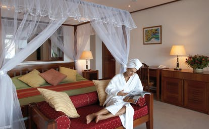 Domaine de la Reserve Seychelles bedroom relaxation woman relaxing on ottoman in front of four poster bed
