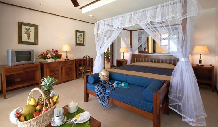Domaine de la Reserve Seychelles bedroom four poster bed white drapes tropical fruit basket