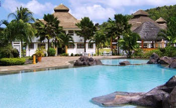 Domaine de la Reserve Seychelles exterior pool white building palm trees