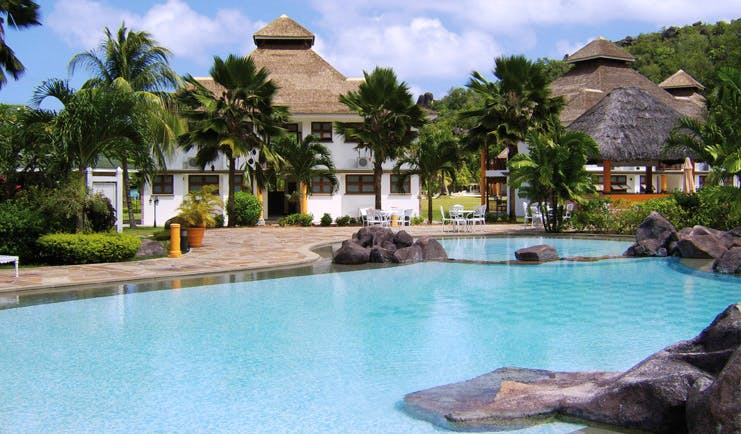 Domaine de la Reserve Seychelles exterior pool white building palm trees