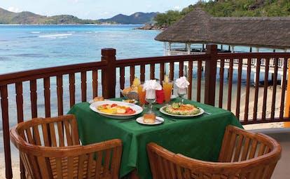 Domaine de la Reserve Seychelles outdoor dining terrace ocean and jetty view