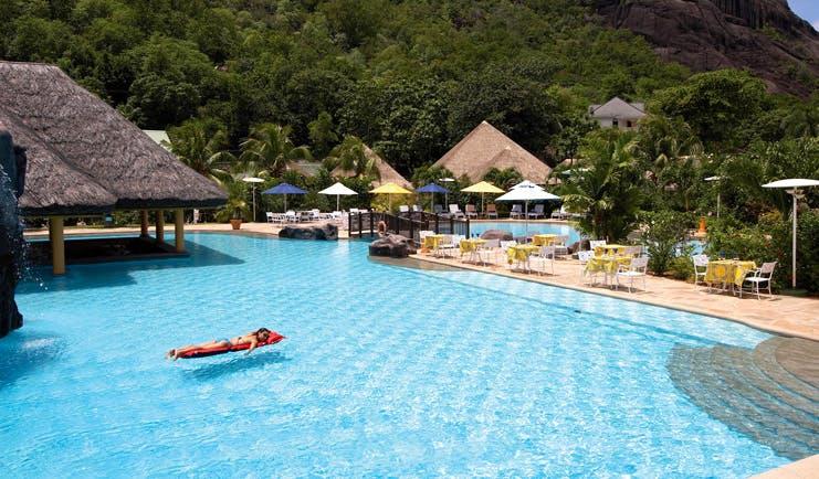 Domaine de la Reserve Seychelles outdoor pool bridge thatched pavilion loungers dining area