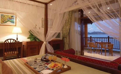 Domaine de la Reserve Seychelles room service tray on bed four poster bed balcony ocean view