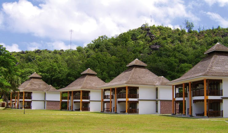 Domaine de la Reserve Seychelles villas white buildings with pointed thatched rooves gardens forest