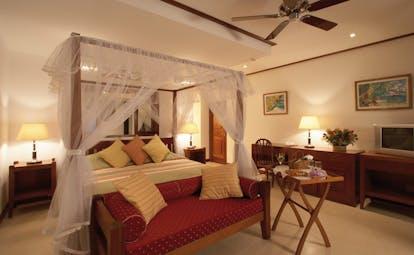 Domaine de la Reserve Seychelles white bedroom four poster white drapes ottoman room service