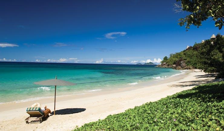 Maia Seychelles beach white sand clear blue waters sun lounger umbrella