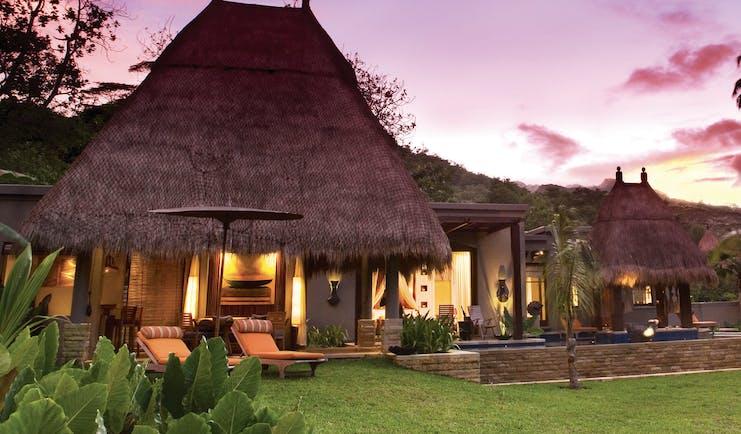 Maia Seychelles villa exterior sun loungers lawn gardens terrace