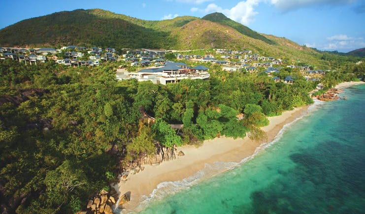 Raffles Praslin resort aerial shot, beach, villas nestled amongst tropical greenery