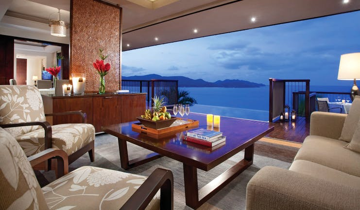 Raffles Praslin royal suite lounge area, sofas, armchairs, open wall with views out across the sea