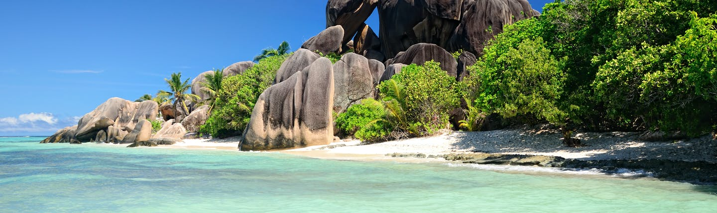 Rock formation and white sandy beach with turquoise blue sea in the Seychelles