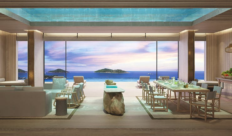 Six Senses Zil Pasyon residence lounge, modern decor, large dining table and sofa, glass walls with views across the ocean to adjacent islands
