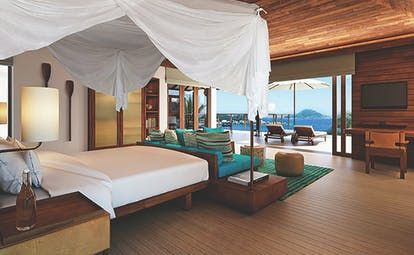 Six Senses Zil Pasyon villa bedroom, bed, sofa, fresh modern decor, terrace with sun loungers and ocean views