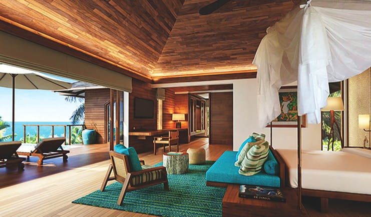 Six Senses Zil Pasyon villa interior, bed, sofa, private terrace with sun loungers