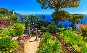 Palms and umbrella pine trees in ornamental garden at Villa Rufolo overlooking deep blue sea