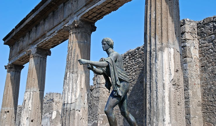 Statue of Apollo stretching out arm at Roman temple in Pompeii