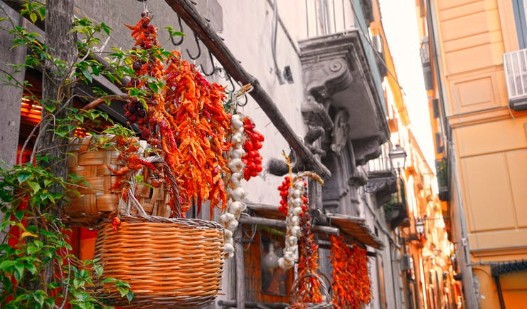 Narrow street lined with baskets and strings of garlic, dried chillies and tomatoes in Sorrento