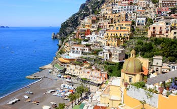 Beach with bright blue sea and dome of church with houses built into the hillside in Positano