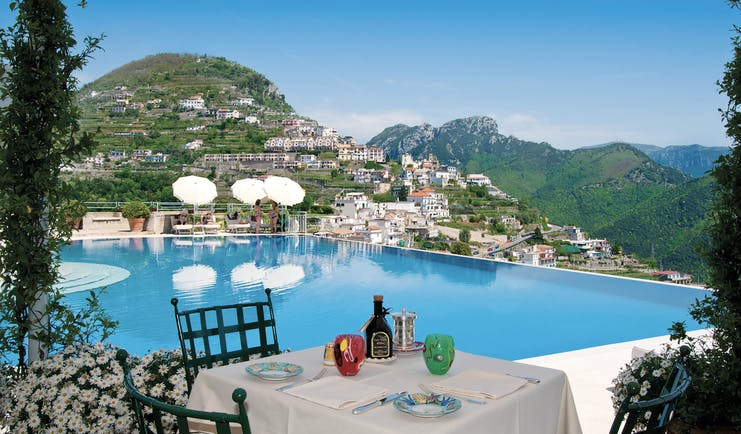 Hotel Caruso Amalfi Coast infinity pool outdoor dining view of mountains