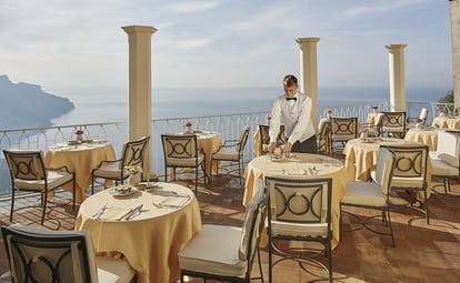 Hotel Caruso Amalfi Coast restaurant terrace waiter dining tables chairs overlooking the sea