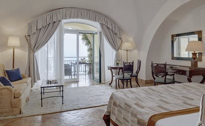 Hotel Caruso Amalfi Coast suite bed and living area doors leading to balcony