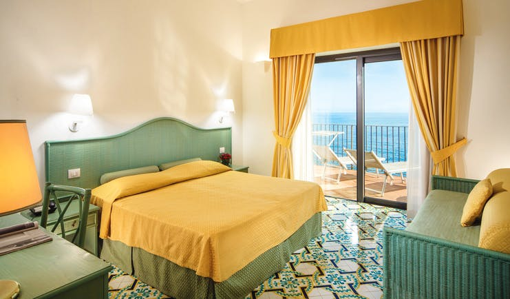 Hotel Miramalfi Amalfi Coast bedroom tiled floors yellow bedding balcony with outdoor seating