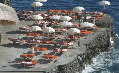 View of the hotel's beach, with red sunbeds and white umbrellas scattered around on the black rocky coast