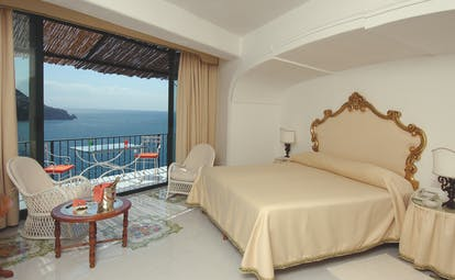 Bedroom at the Il San Pietro di Positano with cream and gold colourings, a large double bed and doors opening up onto a balcony overlooking the sea