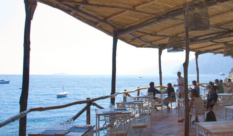 View of the Carlino restaurant looking over the sea, with a beach hut style roof and white table and chairs