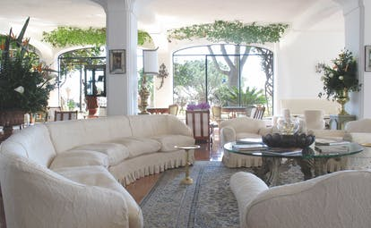 Lobby at the Il San Pietro di Positano with a long curving white sofa, big windows looking out onto the gardens and a cream colour scheme