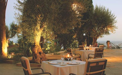 Outdoors restaurant at the Il San Pietro di Positano with palm trees in the background and lights in the trees. A four person table is set