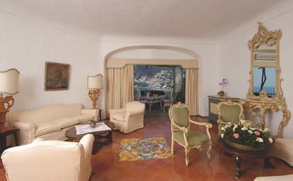 View of a suite living room in the Il San Pietro di Positano with cream sofas, green chairs and large windows leading onto a balcony