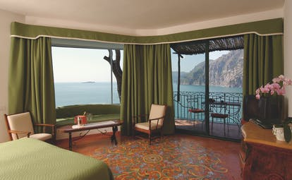 Suite in the Il San Pietro Di Positano with a double bed, sea views and a green colour scheme