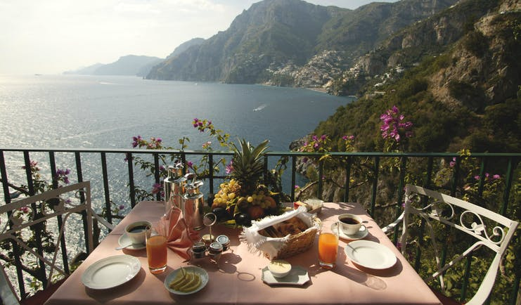 View from the balcony of a terrace suite with a breakfast display laid out on a table, looking over the sea and mountain regions