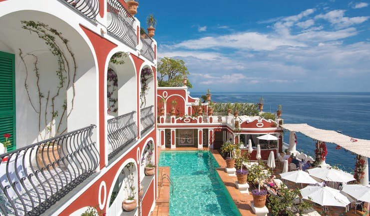 Le Sirenuse Amalfi Coast hotel exterior red building balconies pool ocean in the background