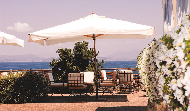 Mezzatorre Resort Amalfi Coast sun terrace outdoor seating area chairs umbrella view of sea