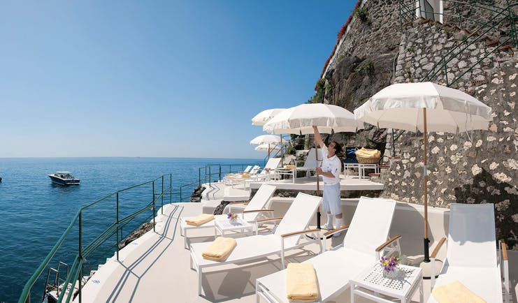 Palazzo Avino Amalfi Coast clubhouse sun loungers umbrellas boats on the water