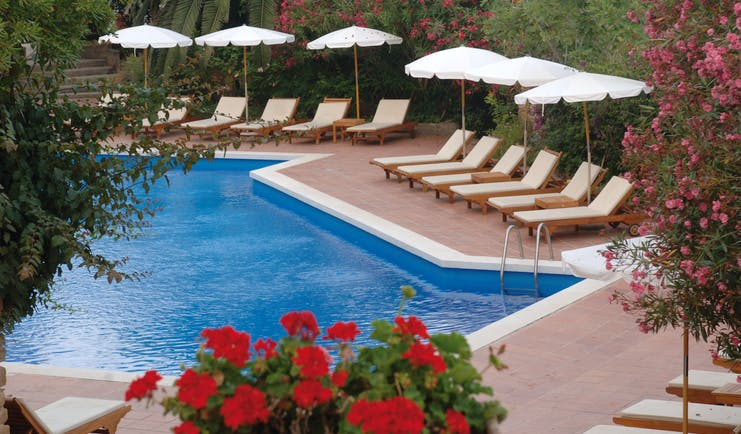 Outdoor pool with sun loungers and umbrellas around the edge of the pool and red flowers around