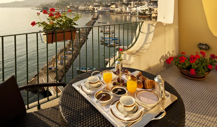 Regina Isabella balcony, breakfast served on sun drenched balcony, overlooking sea and hotel beach club, town and mountains in background