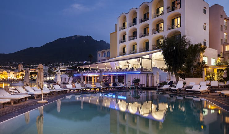 Regina Isabella exterior at dusk, hotel building, pool, sun loungers, town and moutains in background
