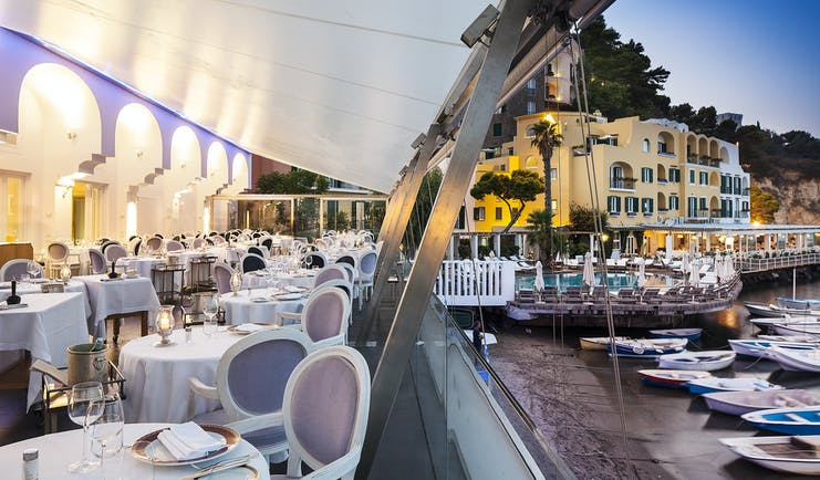 Regina Isabella restaurant, canopied dining area on shoreline, boats moored on sand, elegant tables and chairs