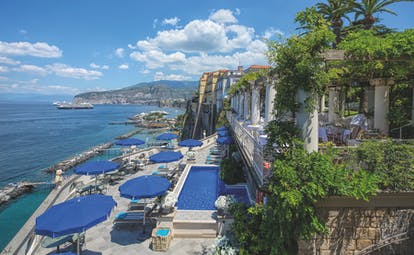 Bellevue Syrene Amalfi Coast pool terrace sun loungers umbrellas ocean coastline in background