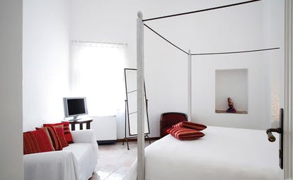 La Locanda Delle Donne Monache Basilicata suite interior four poster bed sofa modern décor