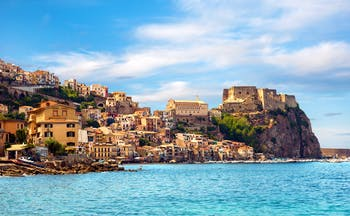 Castle perched on cliff near town overlooking bright blue sea at Scilla in Calabria