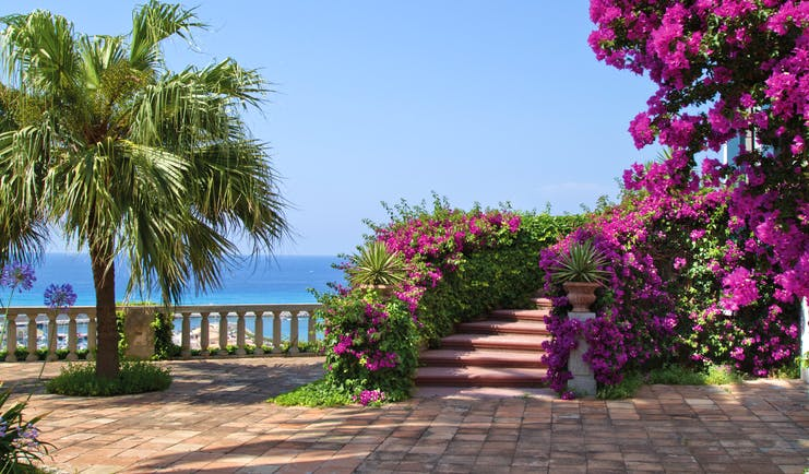 Villa Paola Calabria gardens trees pink flowers views of the sea