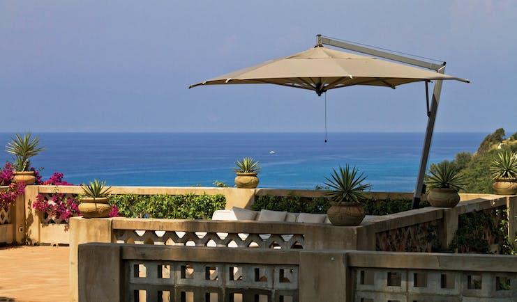 Villa Paola Calabria sun terrace outdoor seating and umbrella overlooking the sea