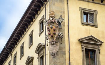 Stone carving of the emblem of the house of Medici on side of wall of building in florence