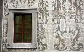 Ornate mural in white on grey stone of a wall in Florence