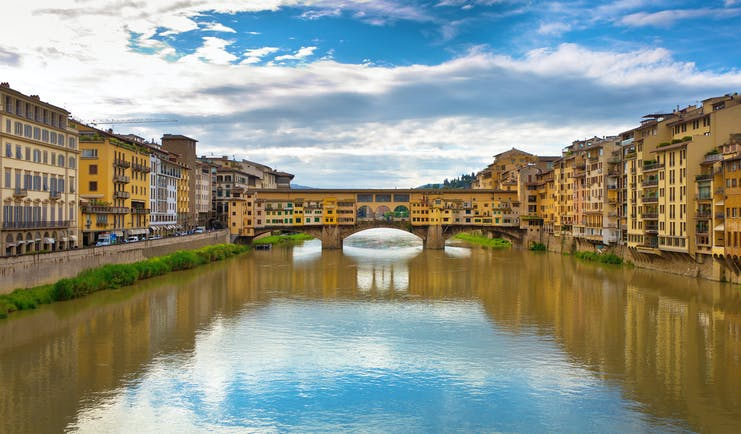 The river Arno with covered bridge Ponte Vecchio joining the two sides of the river in Florence