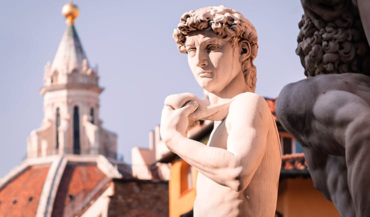 Statue of David with the terracotta cupola of the cathedral in Florence