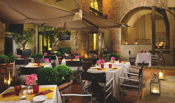 Hotel Brunelleschi Florence courtyard dining outdoor dining area tables set with candles pink flowers